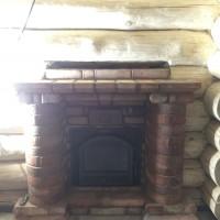 Банная печь Гефест в облицовке змеевиком и порталом под старину из энгельсского кирпича