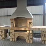 Эконом-вариант летней кухни с мангалом, мойкой и столиком, облицованная искусственным камнем